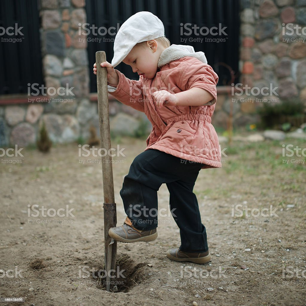 little boy digging a hole stock photo