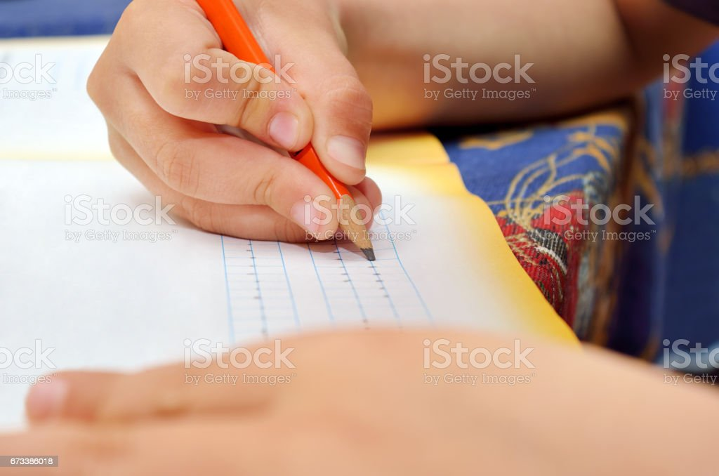 Little boy diligently writes with a pencil in his notebook. Preschool education of children and pedagogy. stock photo