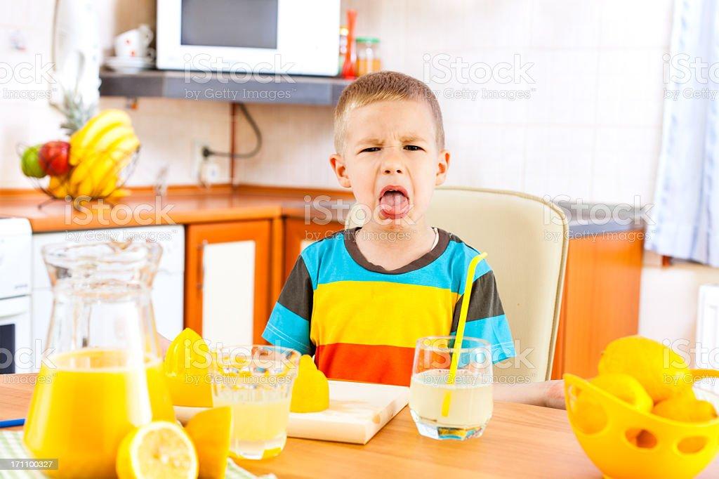 Little boy disliking lemonade and fruits royalty-free stock photo