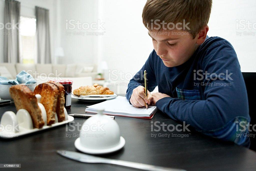 Little boy doing homework at breakfast table stock photo