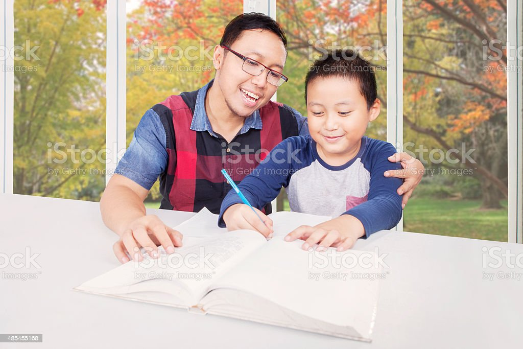 Little boy doing homework with dad stock photo