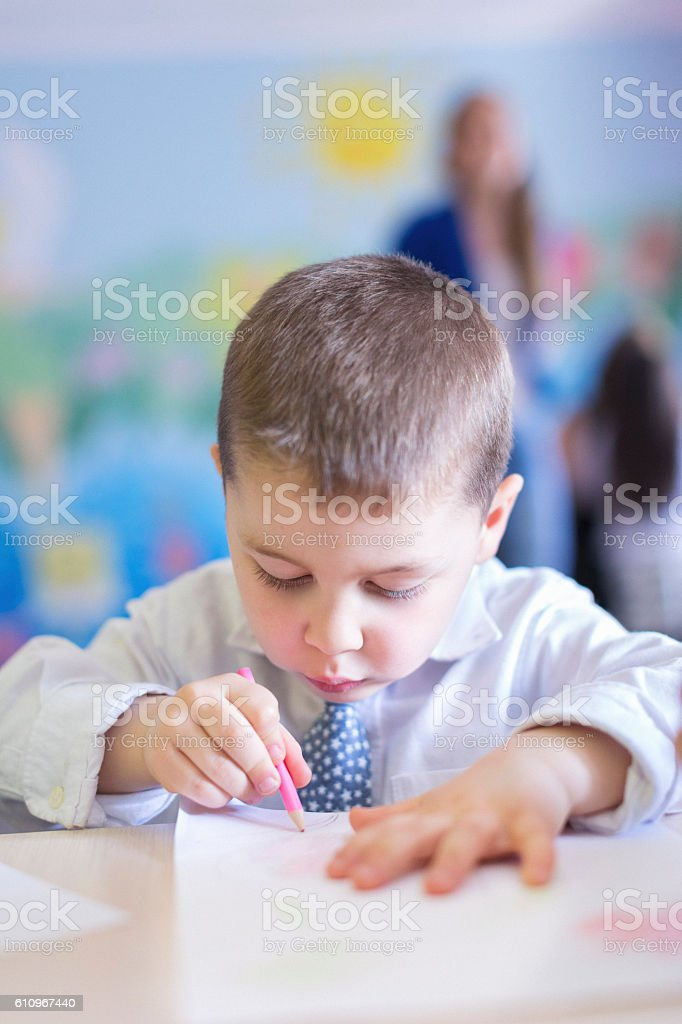 Little boy drawing in classroom stock photo
