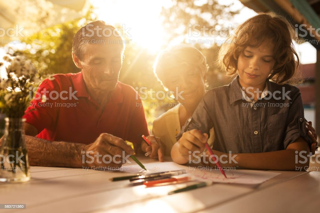 Little boy drawing in the backyard with his grandparents. stock photo