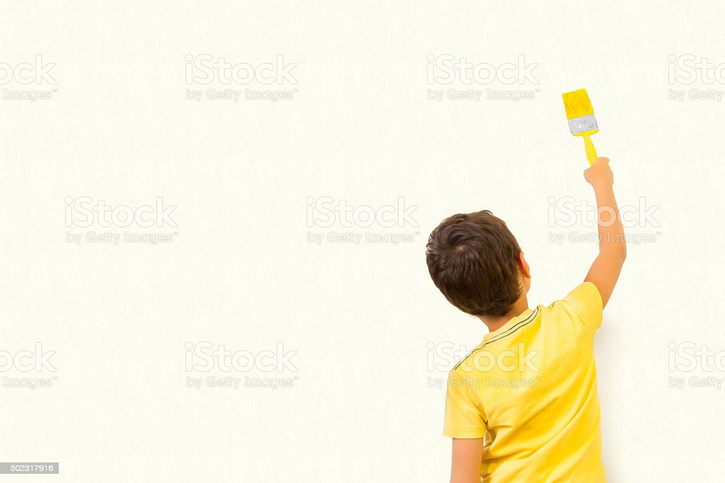 Little boy drawing something on wall background stock photo