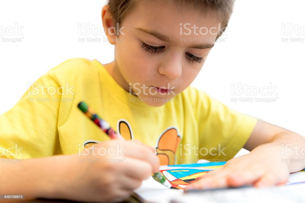 Little boy drawing with colorful pencils stock photo