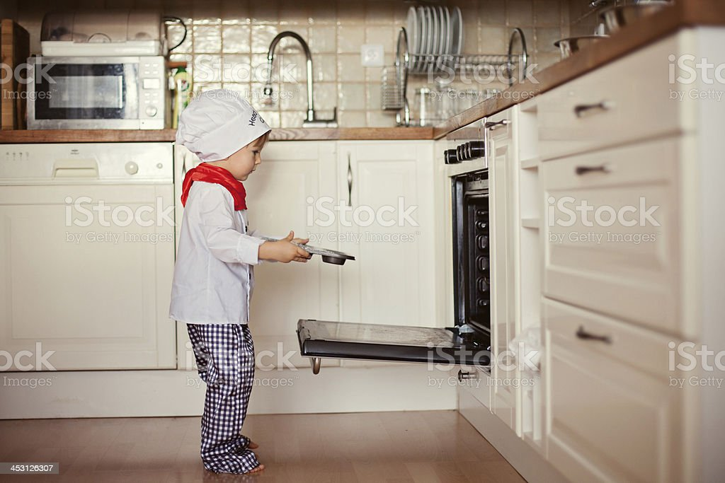 Little boy, dressed like cook, baking muffins stock photo