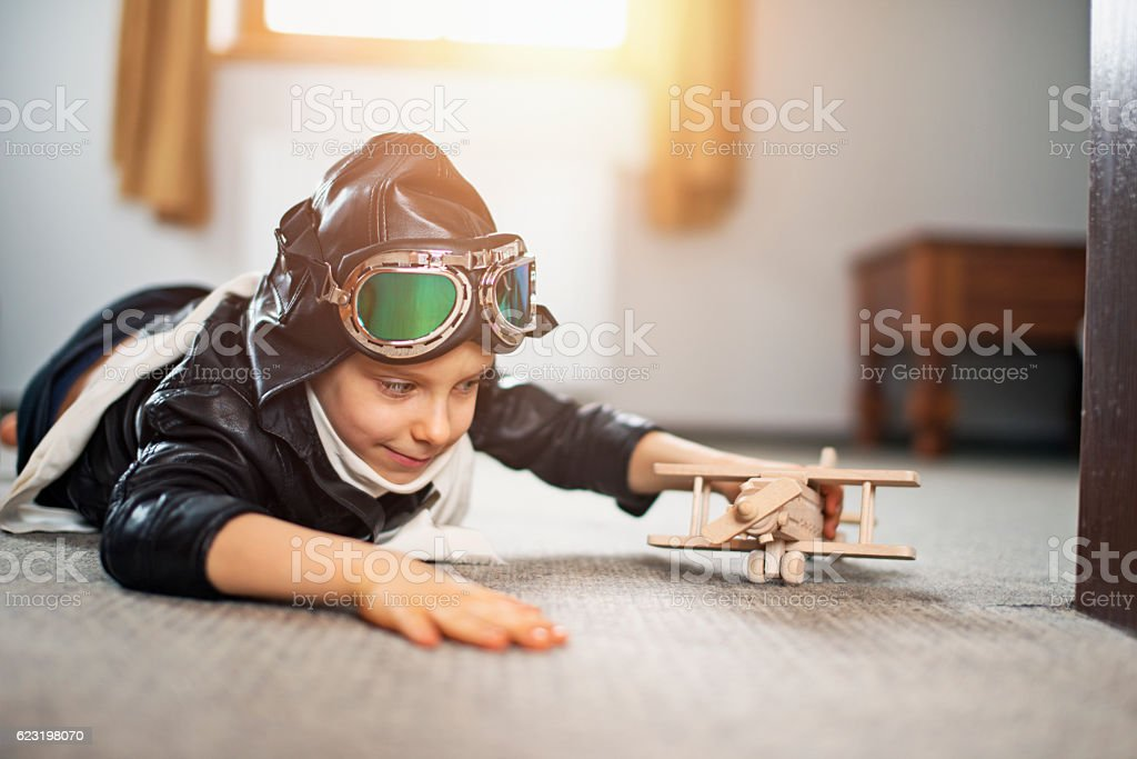 Little boy dressed up as pilot playing with toy plane stock photo