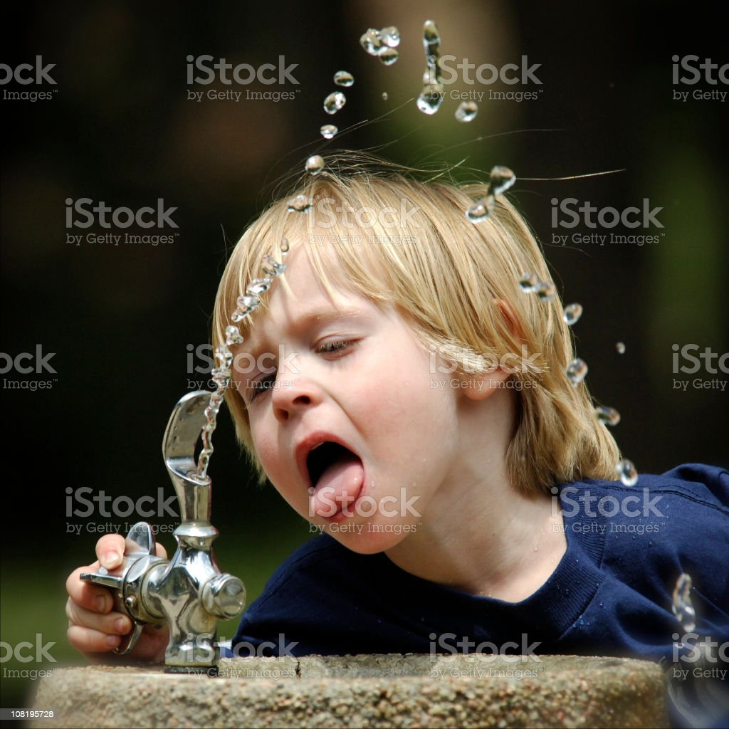 Little Boy Drinking from Water Fountain Outside stock photo