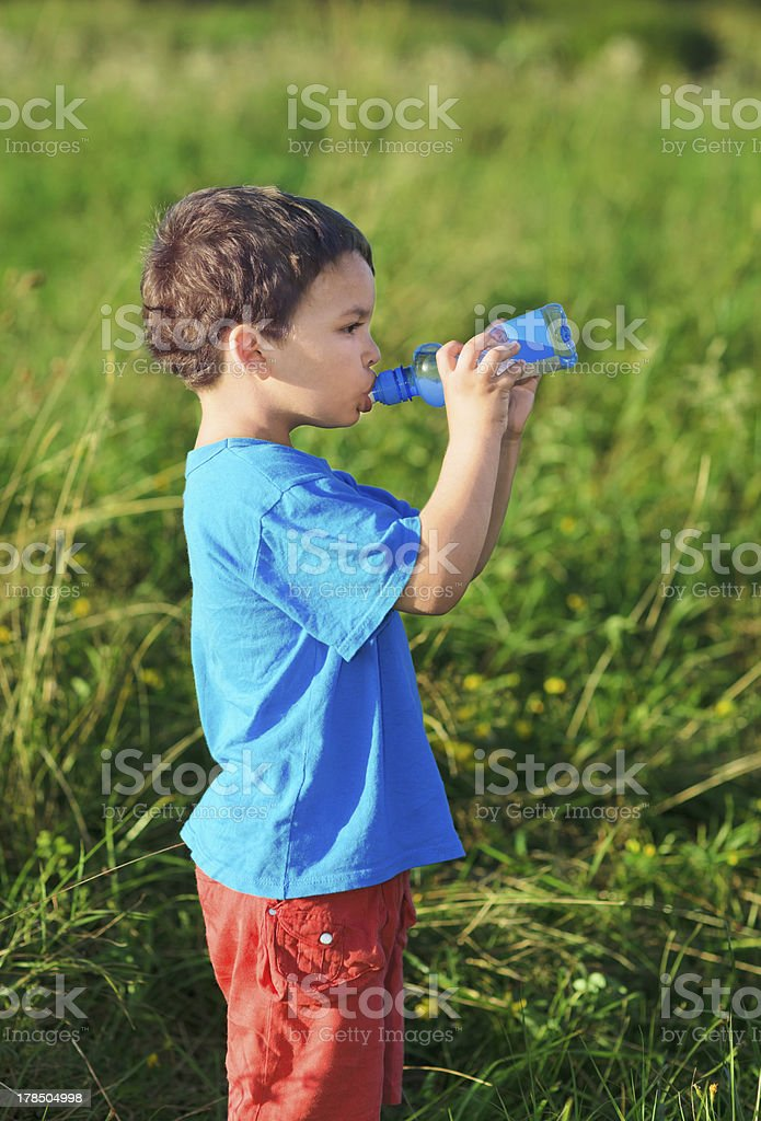 Little boy drinking gas water on green grass field royalty-free stock photo