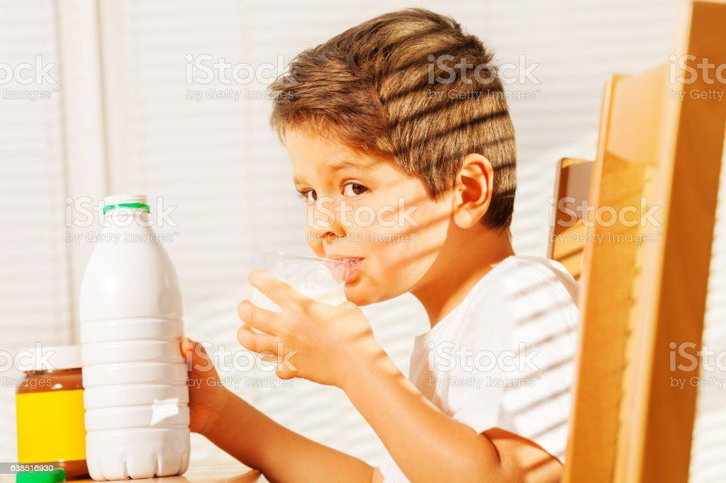 Little boy drinking milk during breakfast stock photo