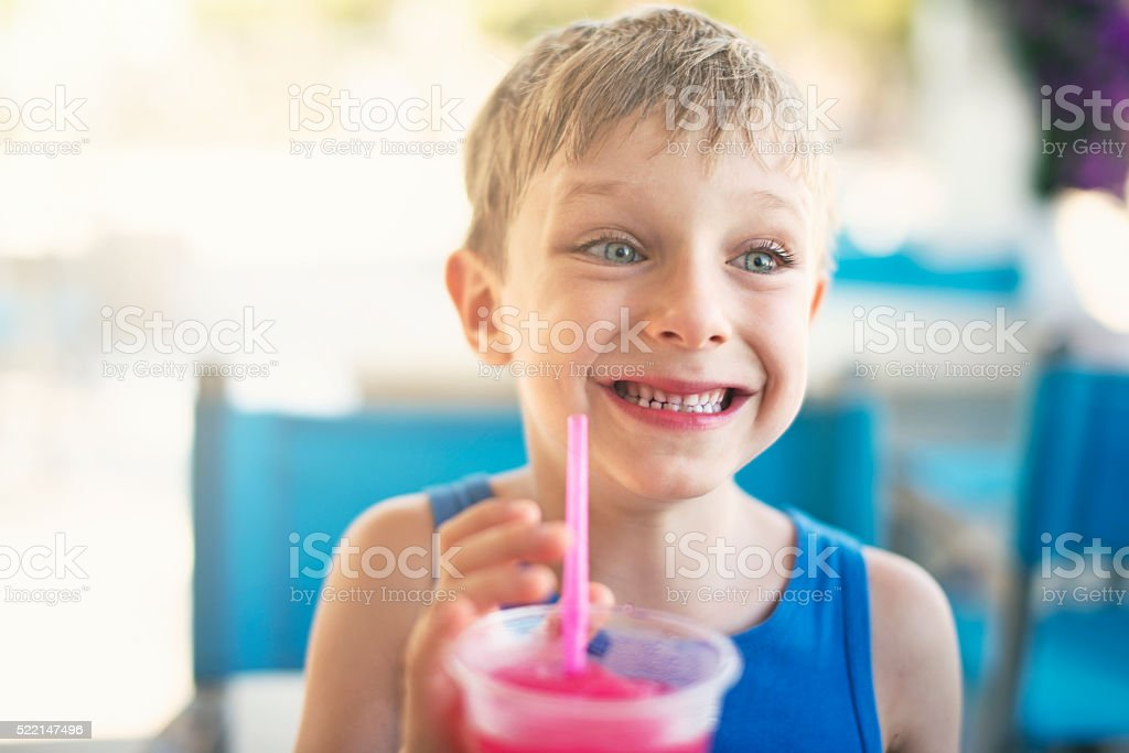Little boy drinking soda with crushed ice on summer day stock photo