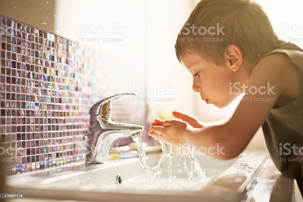 Little boy drinking tap water stock photo