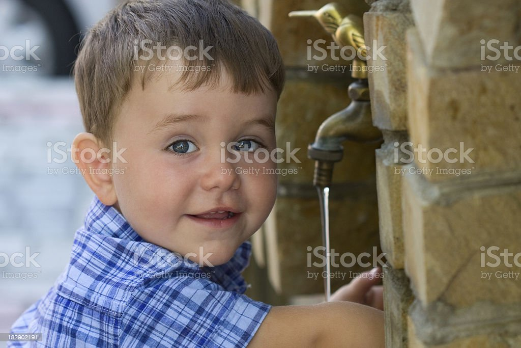 Little boy drinking water from fountain stock photo