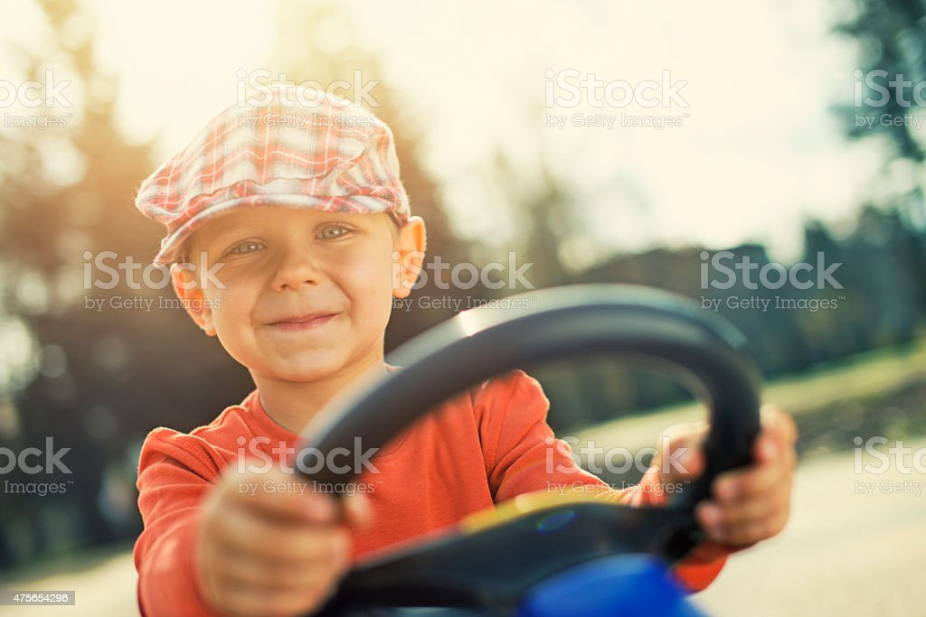 Little boy driving gokart in the park stock photo