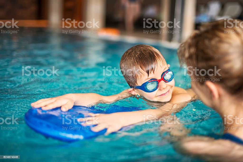 Little boy during swimming lesson at indoors swimming pool stock photo