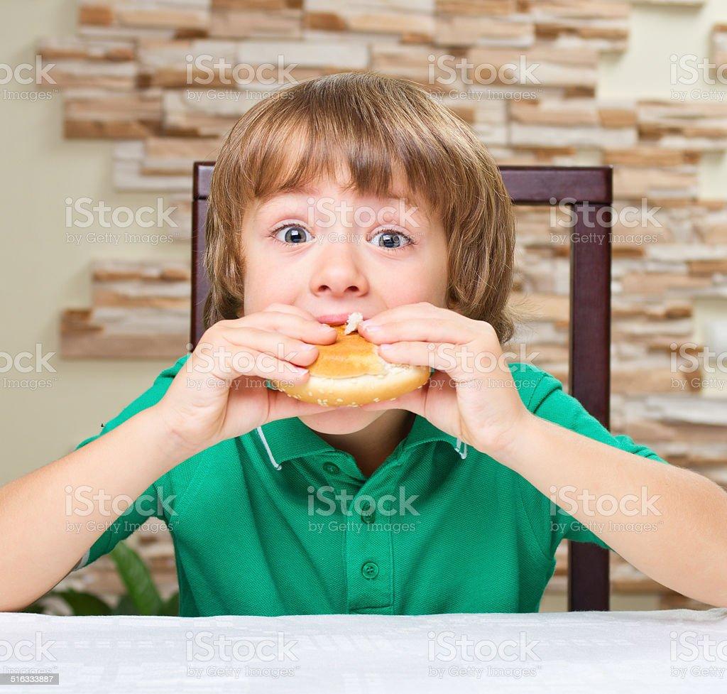 Little boy eat hamburger stock photo