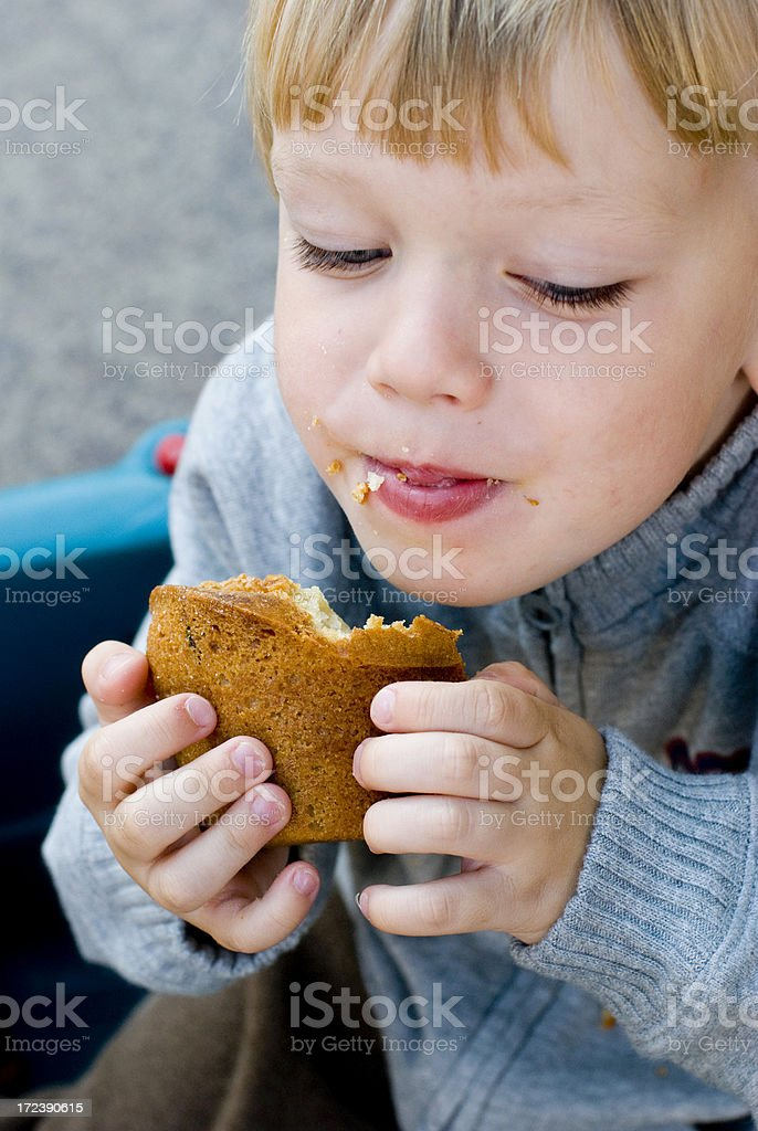 Little boy eating a muffin royalty-free stock photo