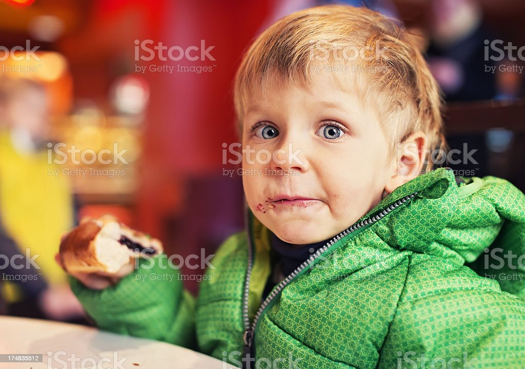 Little boy eating a sweet bun royalty-free stock photo