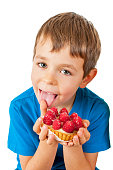 Little boy eating cakes with fruits.