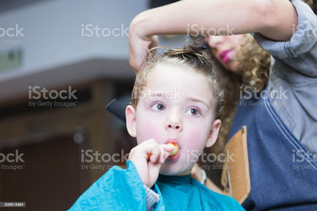 Little boy eating candy in barber chair stock photo