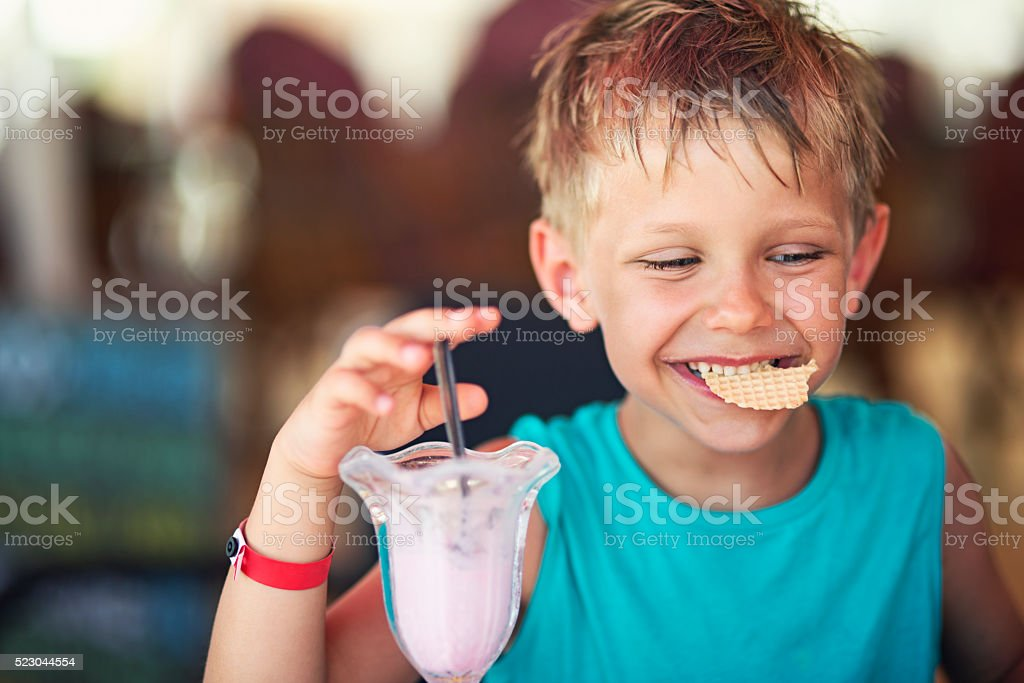 Little boy eating ice cream at restaurant stock photo