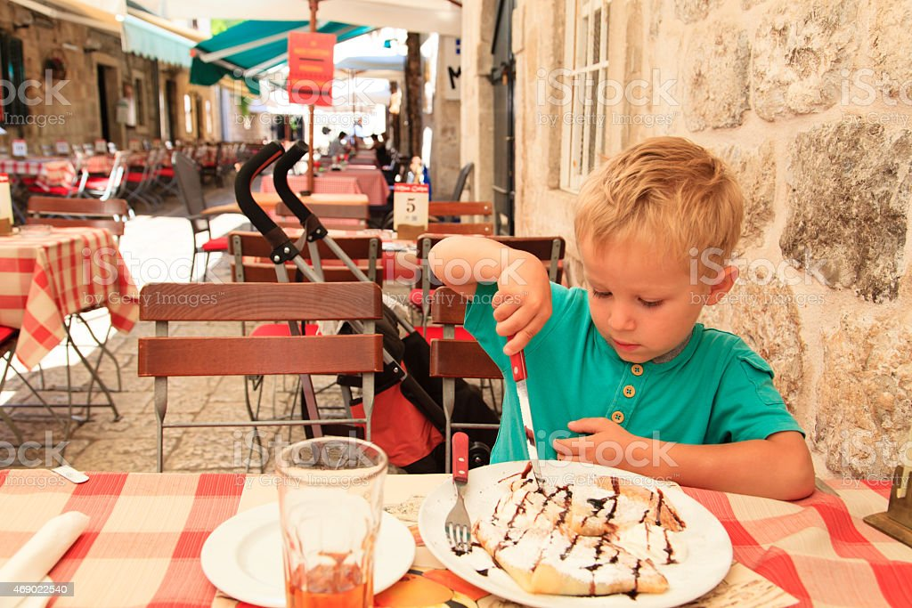 little boy eating in city cafe on summer day stock photo