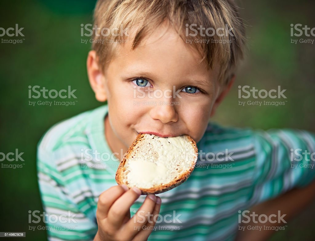 Little boy eating loaf of bread with butter stock photo