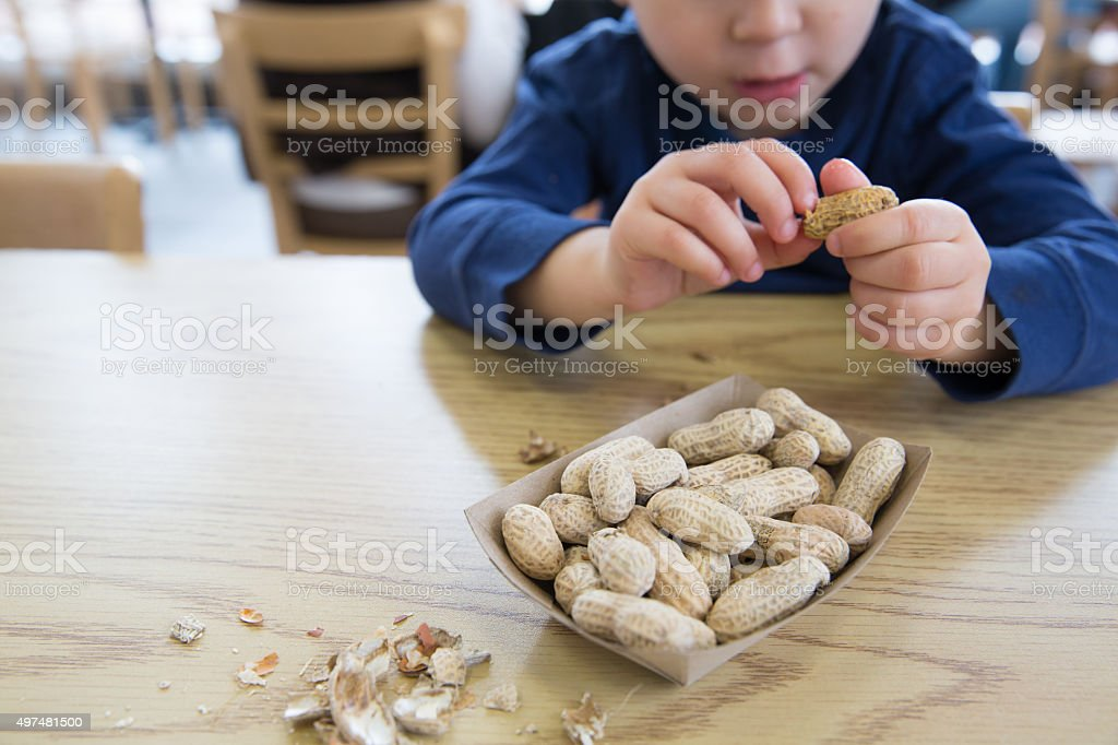 Little boy eating peanuts stock photo