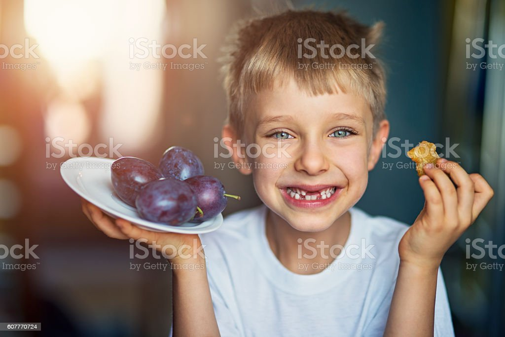 Little boy eating plums at home stock photo