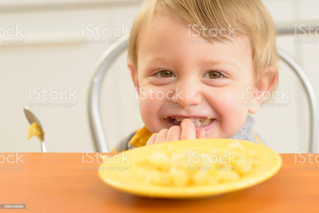 Little Boy Eating Potatoes stock photo
