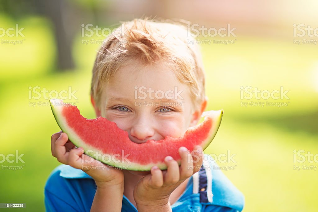 Little boy eating watermelon outdoors stock photo