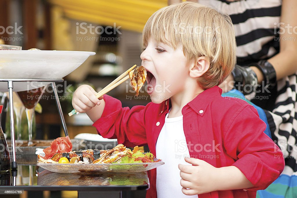 Little boy eats Japanese food royalty-free stock photo