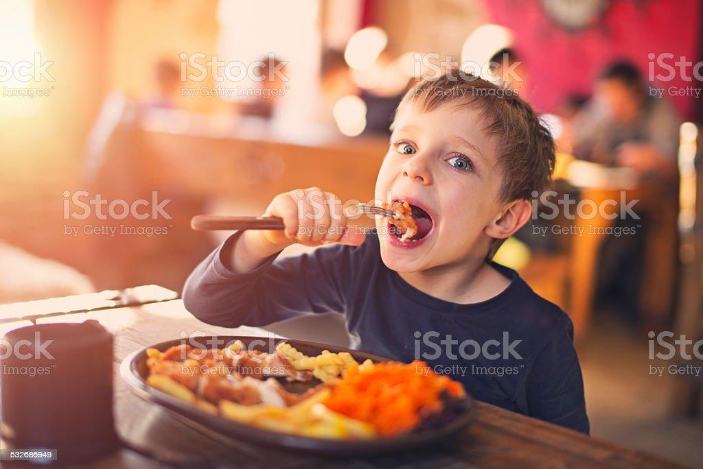 Little boy enjoying dinner at the restaurant stock photo