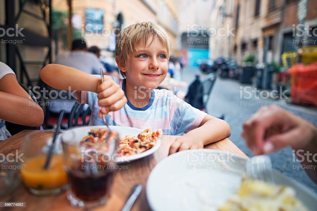 Little boy enjoying lunch in Rome street restaurant stock photo