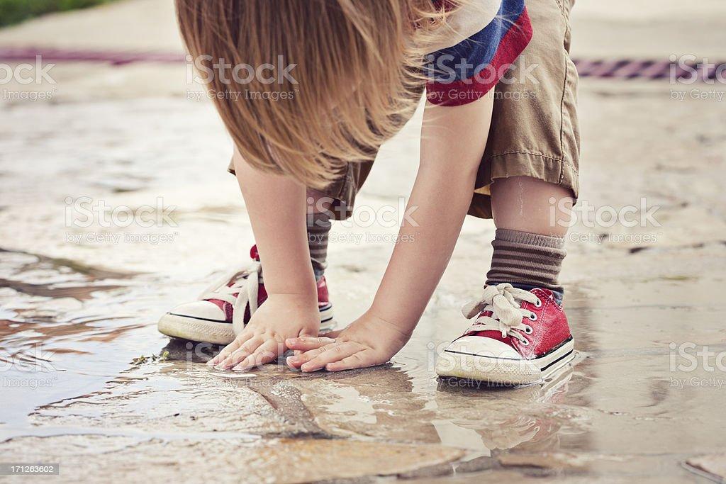 Little boy enjoying the summer rain puddle royalty-free stock photo