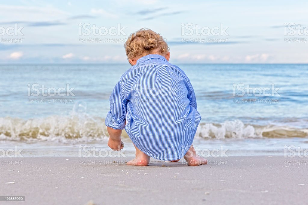 Little Boy Enjoys Playing in the Sand at the Beach stock photo