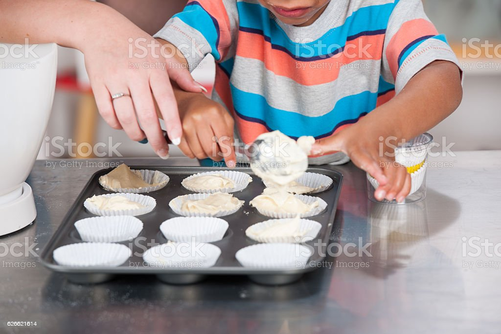 Little Boy Filling Cupcake Liners with Help stock photo