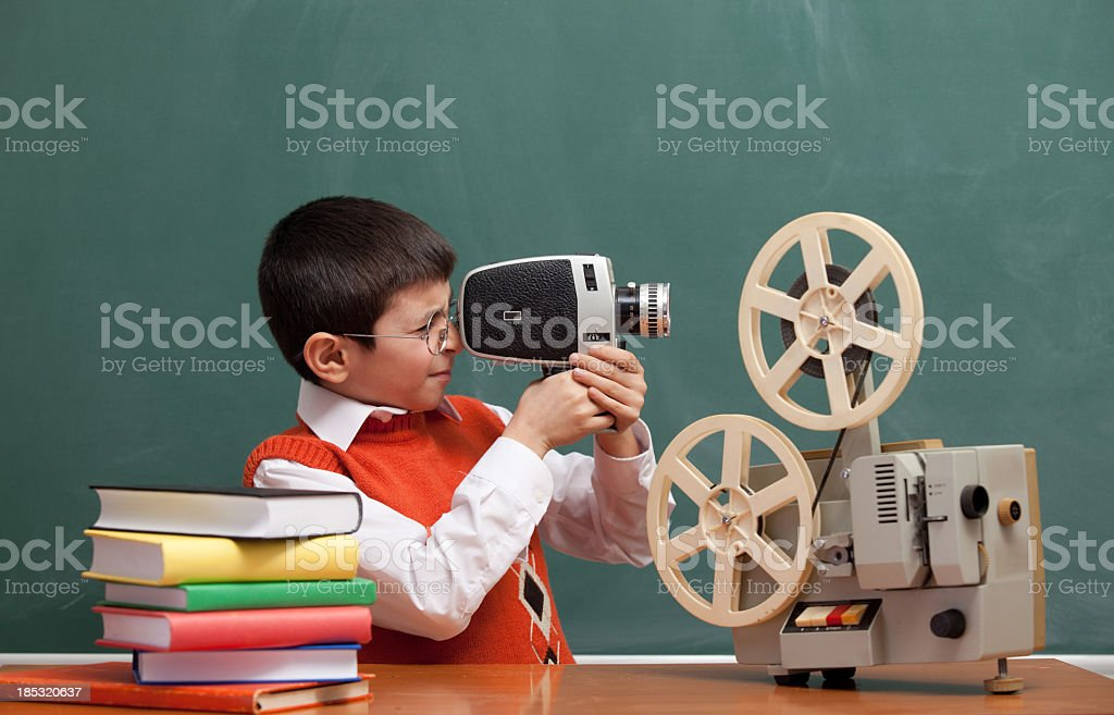 Little Boy Filming With Video Camera In Front Of Blackboard stock photo