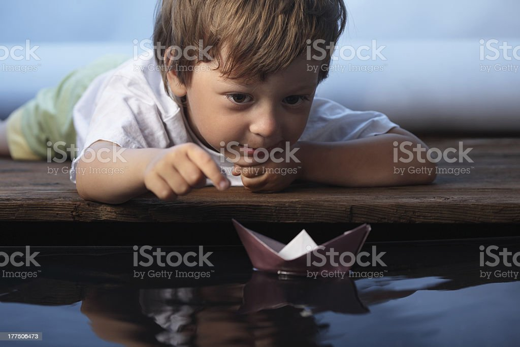 A little boy floating a paper ship stock photo