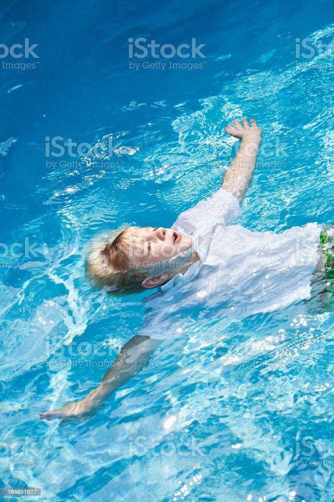 Little boy floating on back stock photo