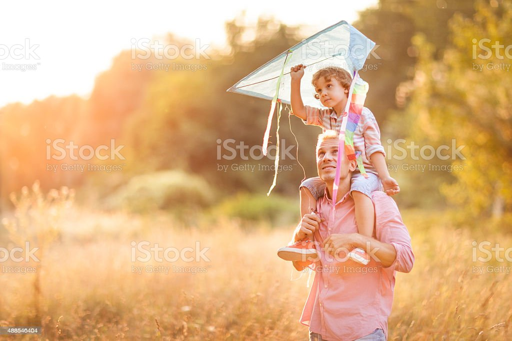 Little boy flying a kite with his father stock photo