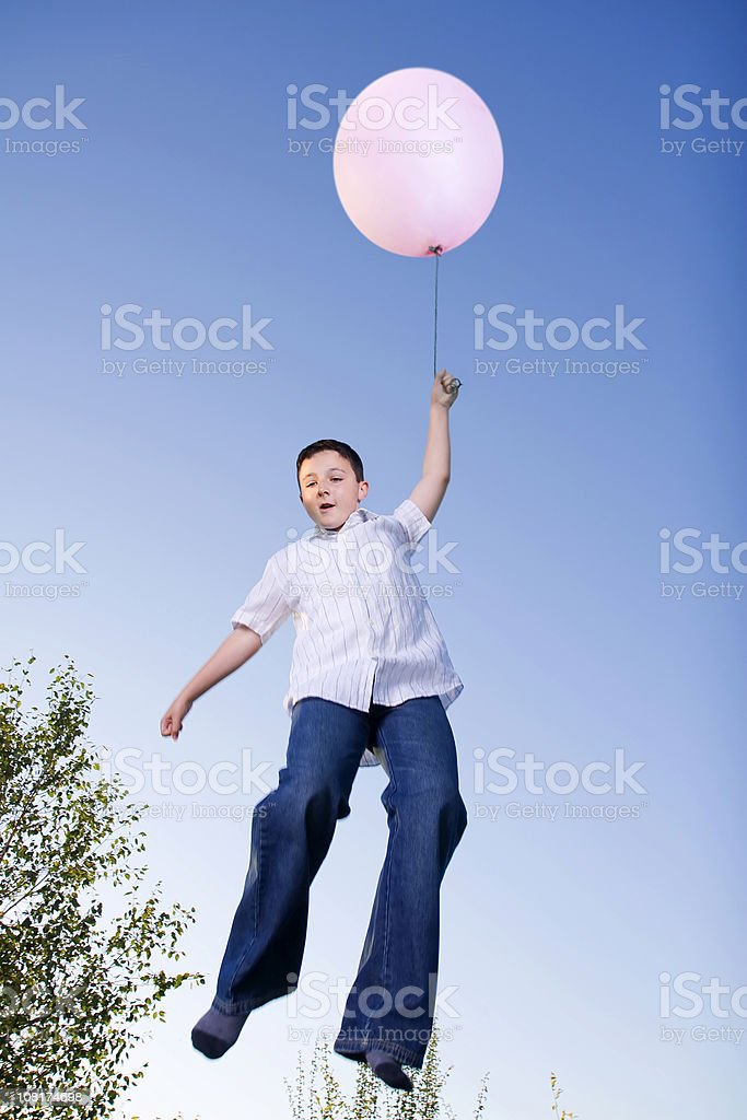 Little Boy Flying with Pink Balloon stock photo