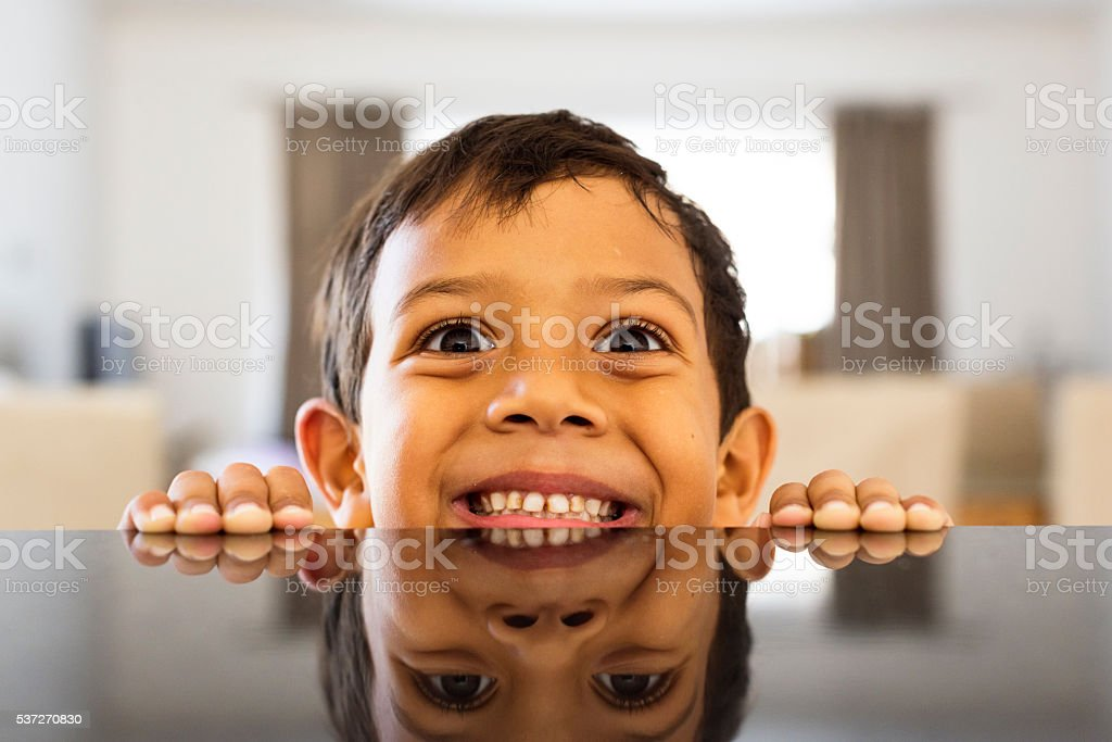 Little Boy Fooling Around At The Kitchen Counter stock photo