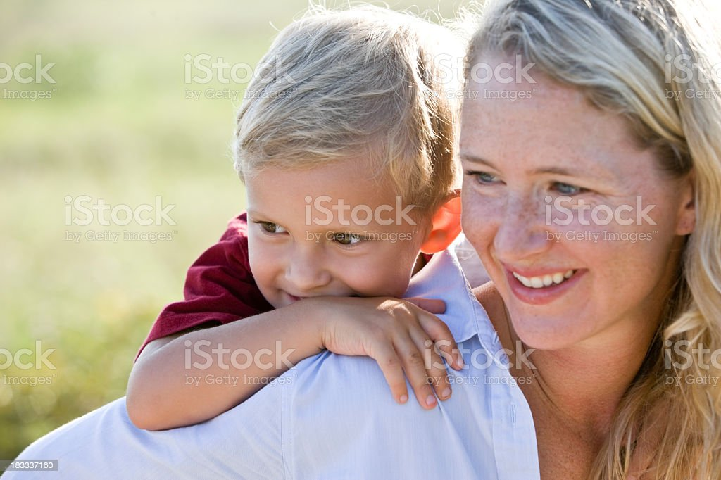 Little boy getting piggyback ride, watching over mother's should royalty-free stock photo