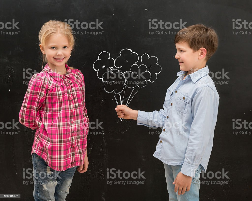 little boy givig drawn flowers to the smiling  girl stock photo