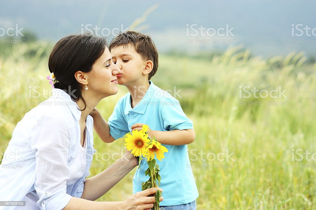 Little boy giving flowers and kiss to mother royalty-free stock photo