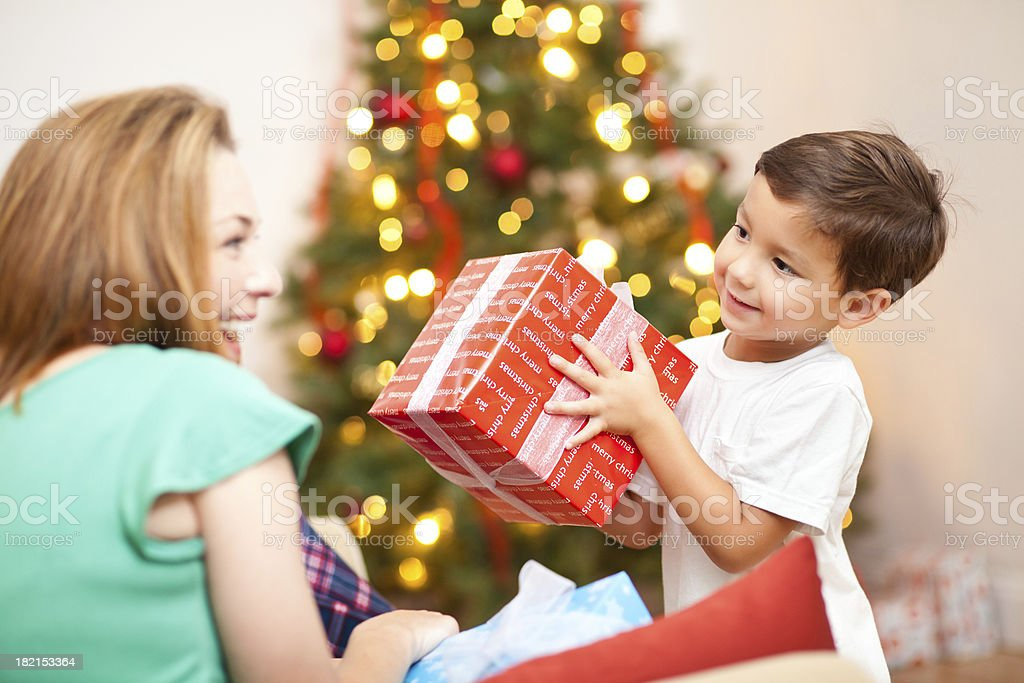 Little Boy Giving Present to Mom on Christmas Morning royalty-free stock photo
