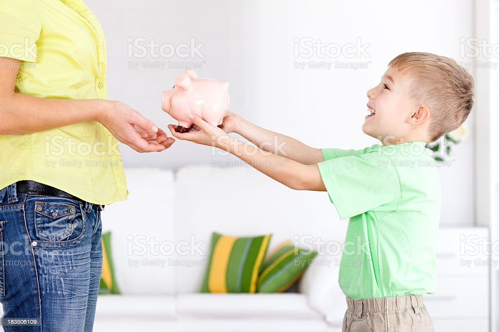 Little boy giving savings and piggy bank to his mother royalty-free stock photo
