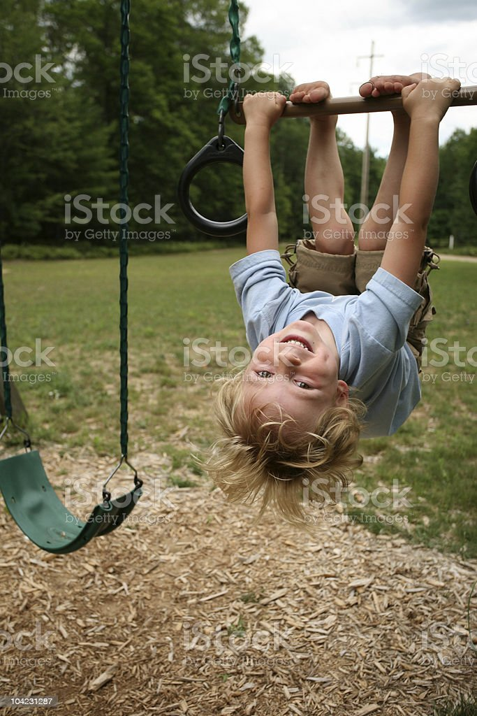 A little boy hanging upside down from a swing set stock photo