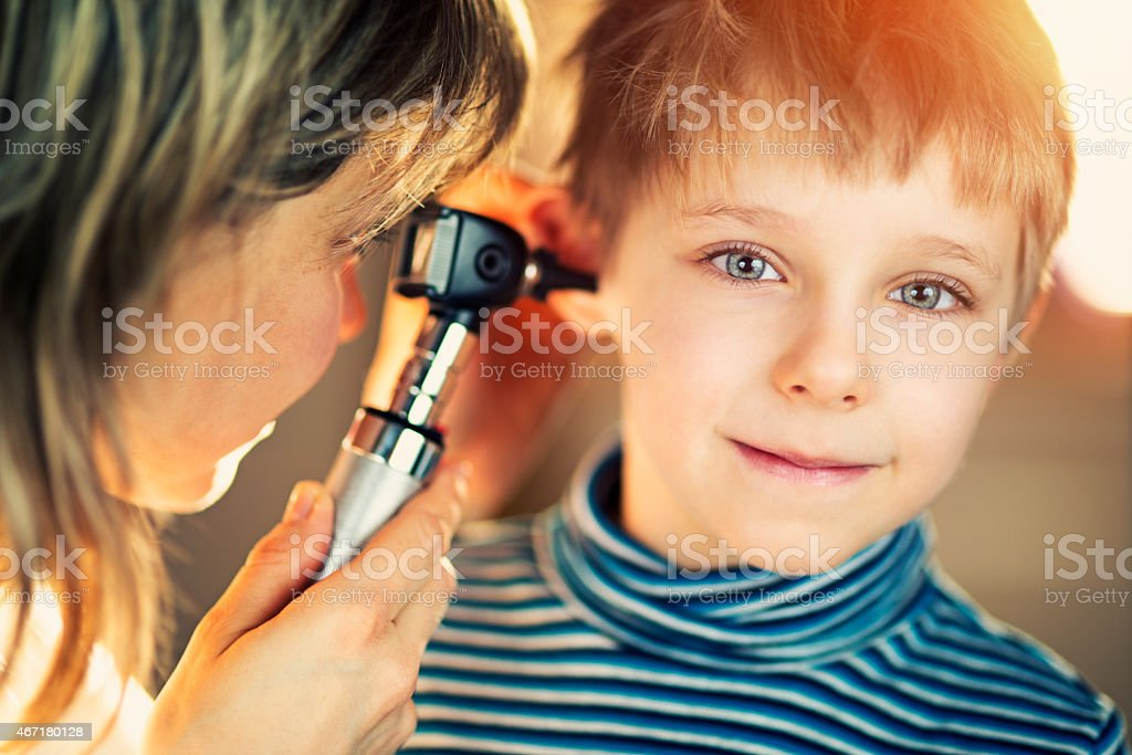 Little boy having ear examination at home. stock photo
